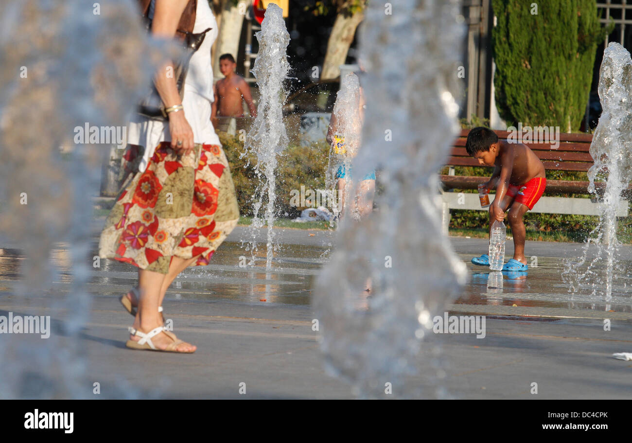Kids refresh playing over floor fountains during a heat wave with temperatures around 40degrees in Mallorca, the - Stock Image