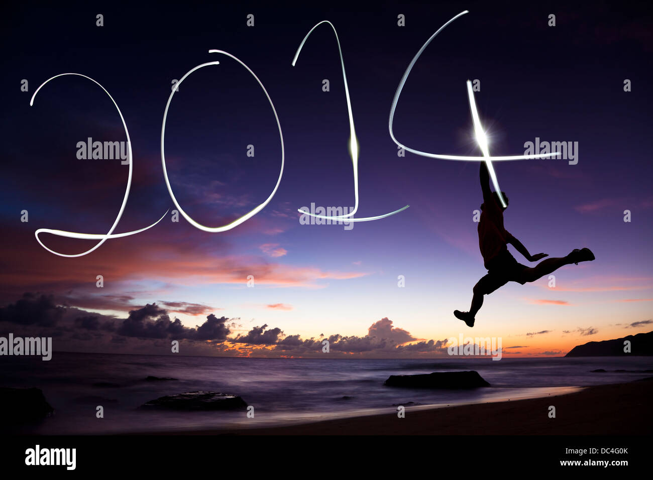 happy new year 2014.young man jumping and drawing 2014 by flashlight - Stock Image