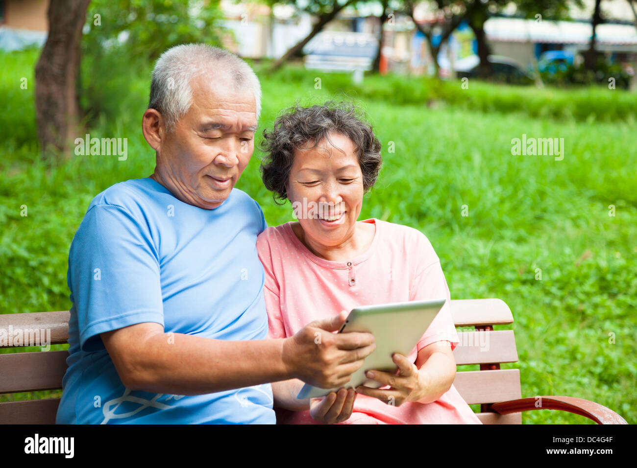 happy seniors couple with tablet pc in the park - Stock Image