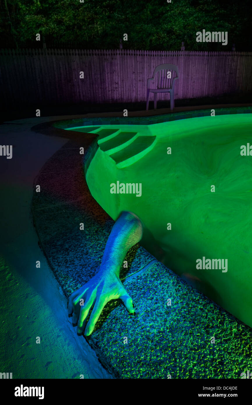 Creepy Scary Arm Reaching Out Of Swimming Pool - Stock Image