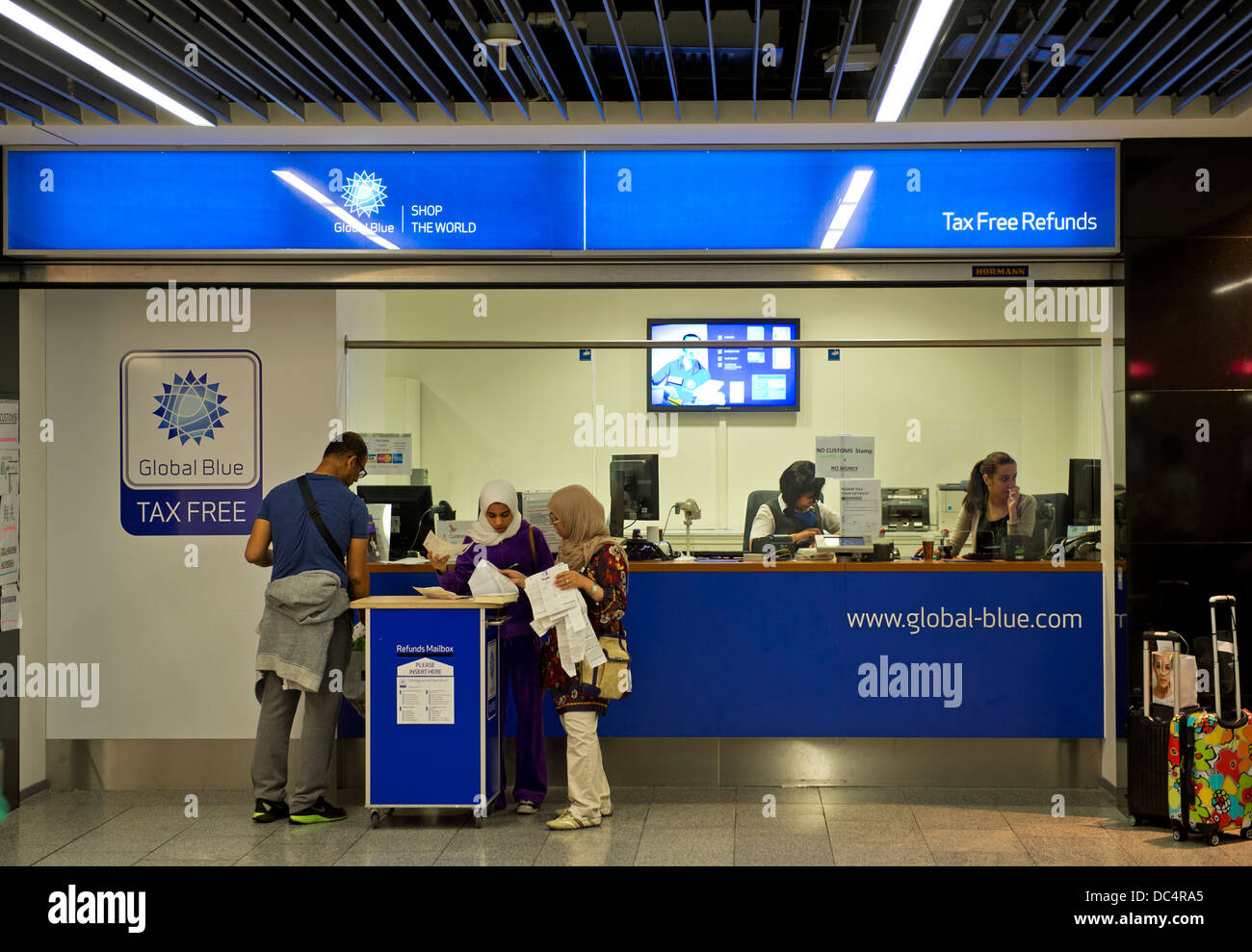 Asian tourists at a counter of Global Blue Tax Free company for refunding the German VAT, Frankfurt airport, Frankfurt, - Stock Image