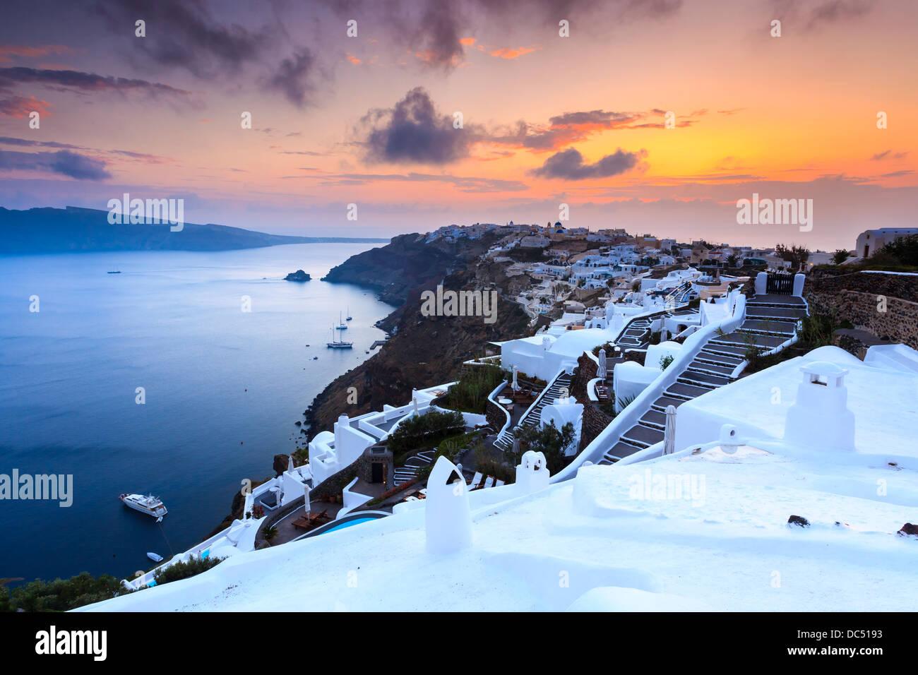 The sun settings over the beautiful village of Oia on the Island of Santorini Greece. - Stock Image