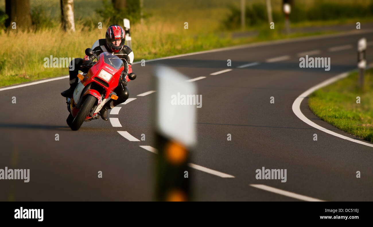 Motorcyclist on his Ducati in a curve on a rural road - Stock Image