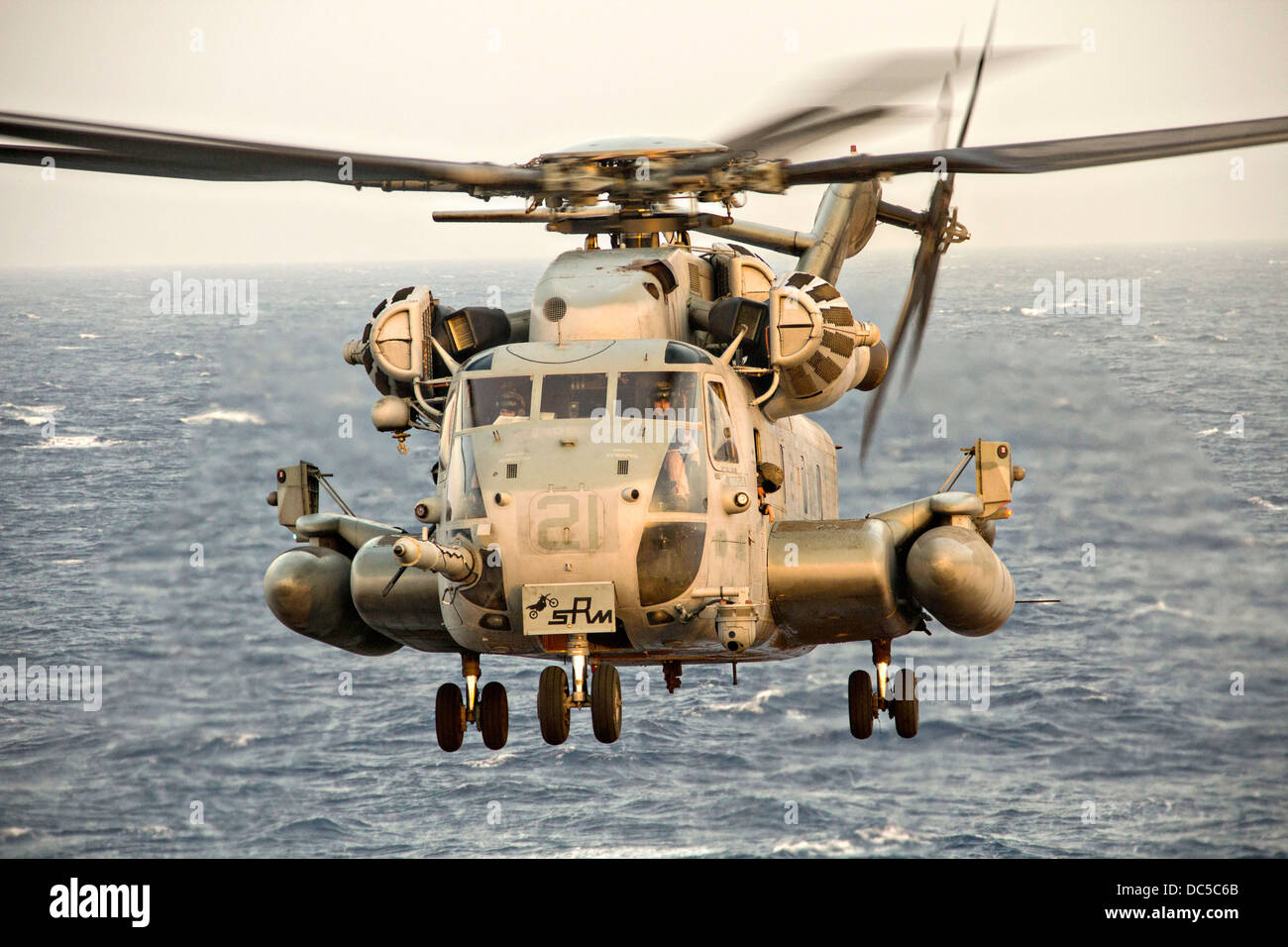 A US Marine Corps CH-53E Super Stallion helicopter prepares to land on the flight deck of the USS San Antonio July - Stock Image