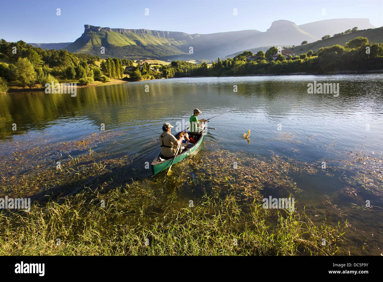 Fishing in a canoe, reservoir of Maroño, Sierra Salvada in background, Alava, Basque Country, Spain - Stock Image