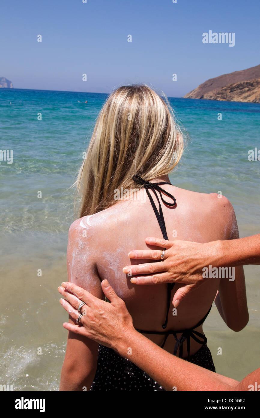Mother puts suncream on her daughter to prevent sunburn - Stock Image
