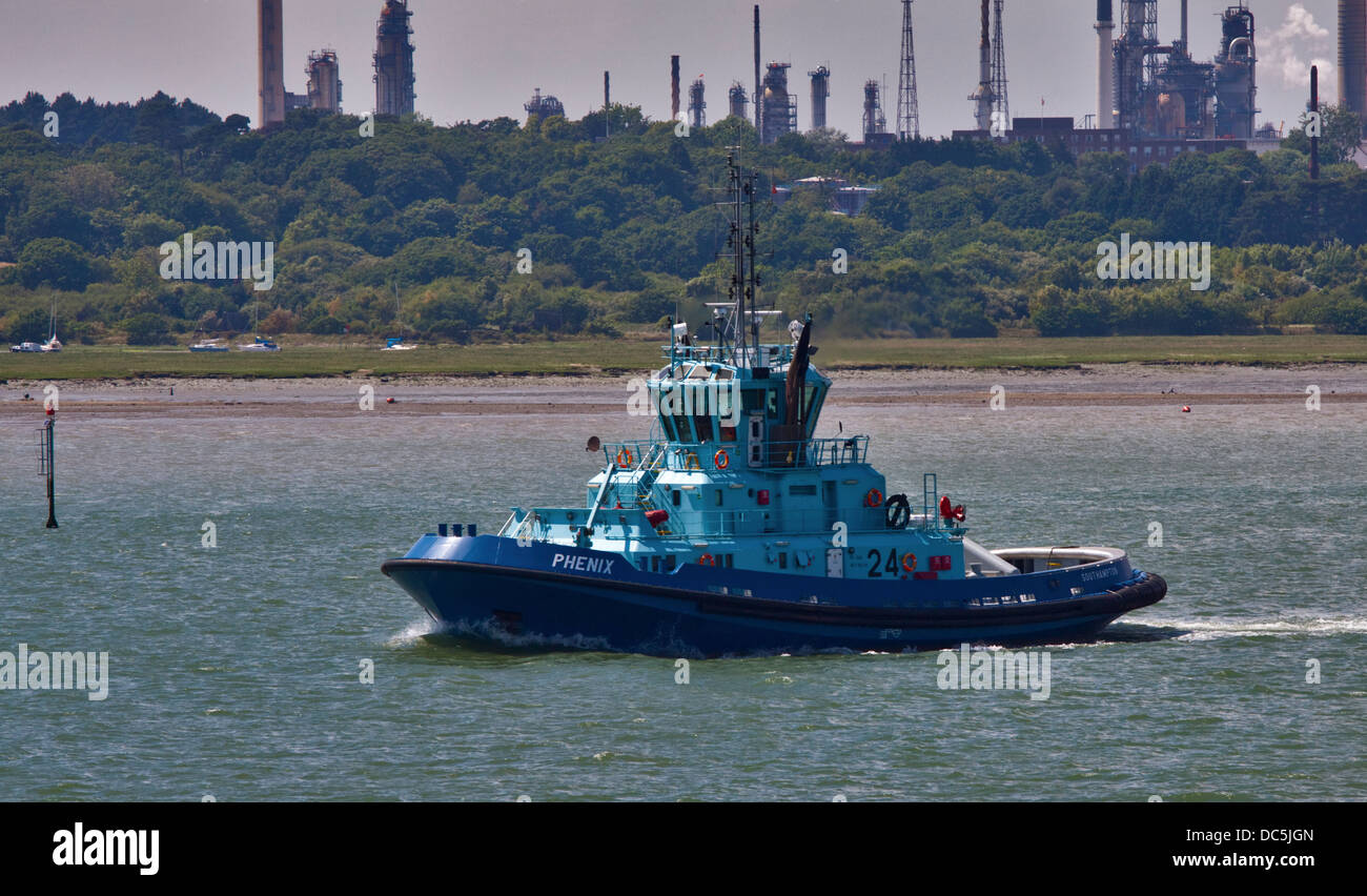 Pilot Boat Phenix sailing past Fawley Oil Refinery, Southampton Water, Hampshire, England - Stock Image