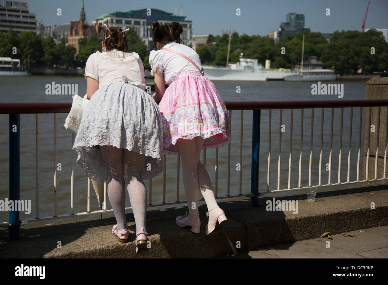 Two girls wearing Lolita dresses lean over the barrier over the River Thames on the South Bank, London, UK. Lolita - Stock Image