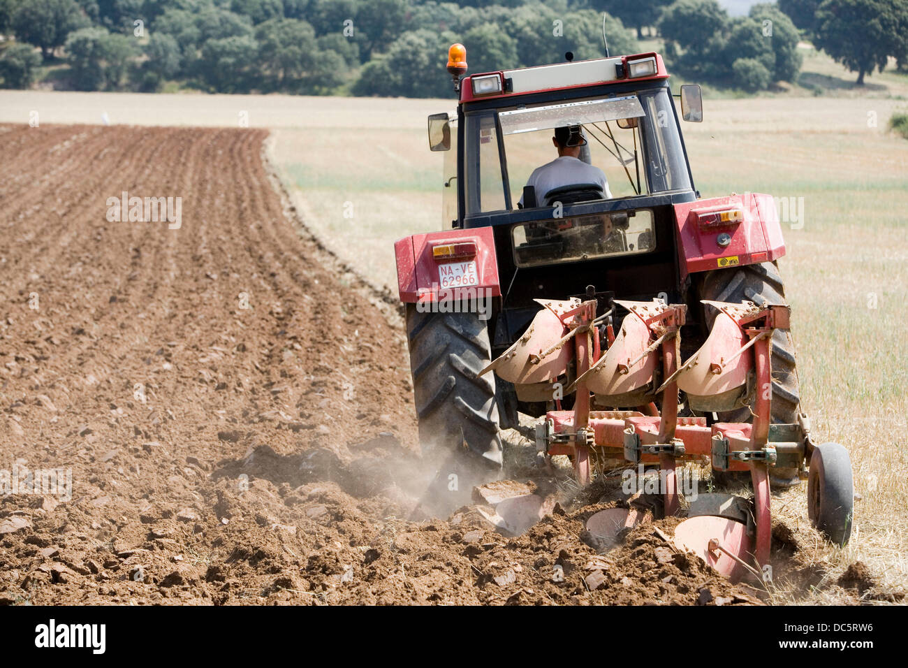 Agricultural machinery. Tractor ploughing the land. Mouldboard plough. Harvesting of cereals, Oco (near Estella), - Stock Image