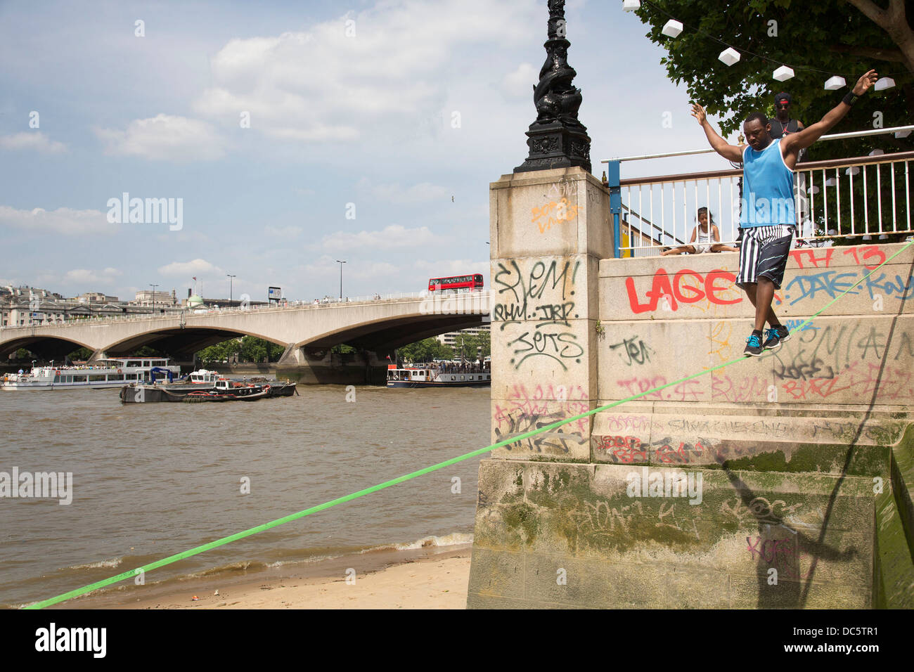 Slackliner practices on the river wall down to the beach on the River Thames at the Southbank. South Bank is a significant - Stock Image