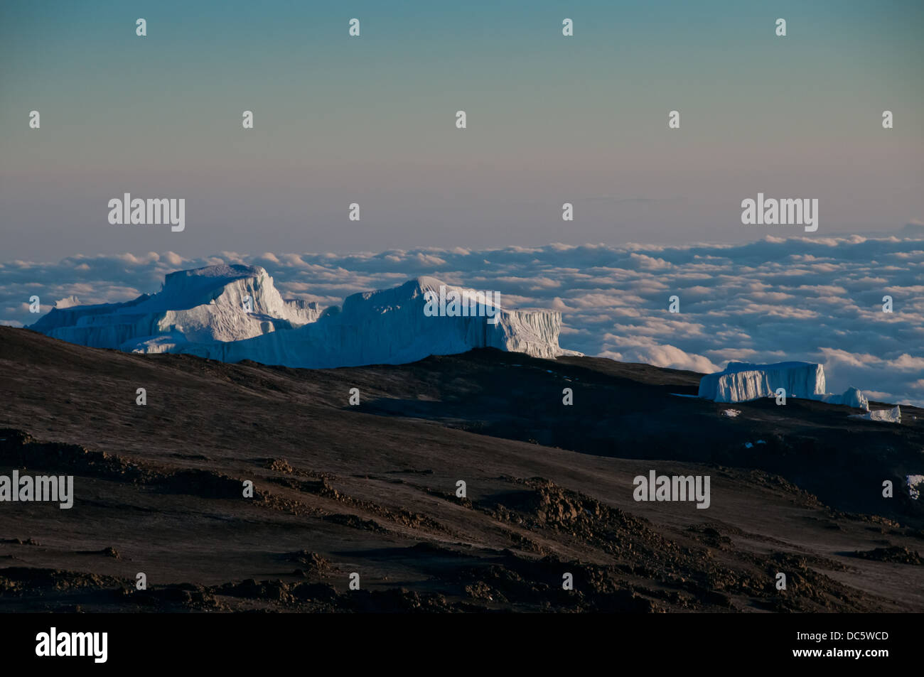 High above the clouds the early morning sun beginning to appear on the glaciers on the crater rim of Kilimanjaro - Stock Image