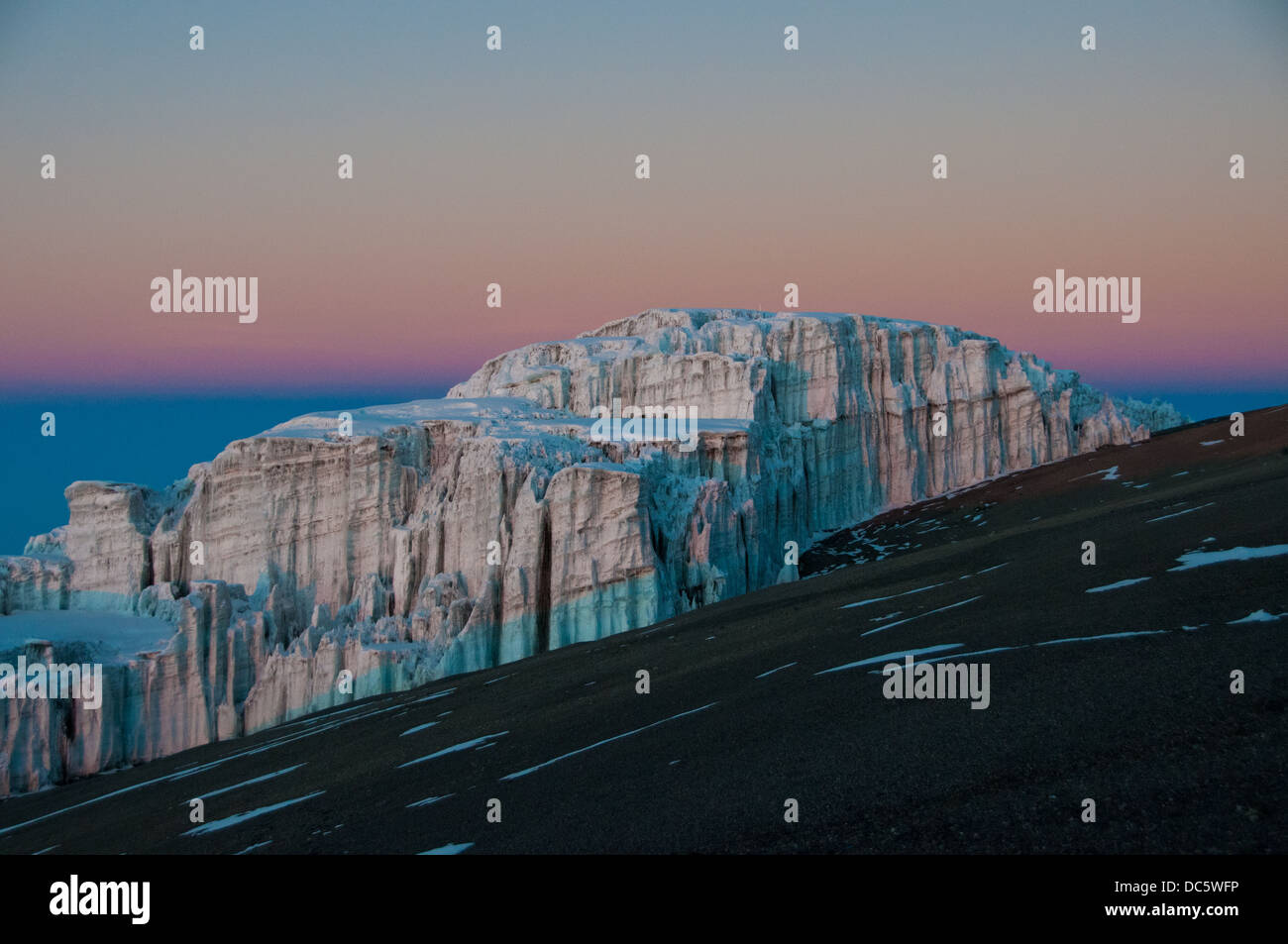 The early morning sun beginning to appear on the glaciers on the crater rim of Kilimanjaro - Stock Image
