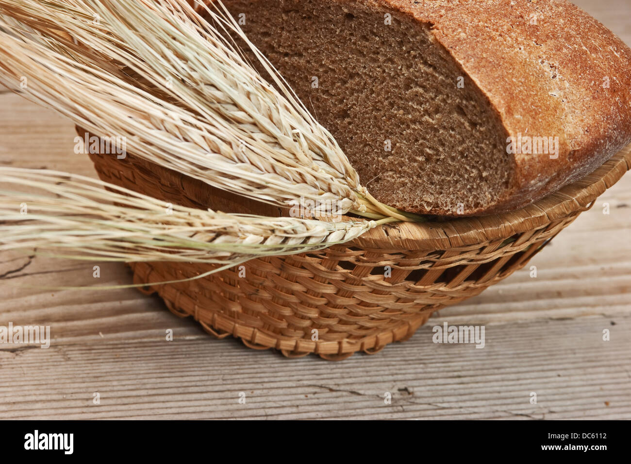 rye bread and ears of corn in the basket - Stock Image