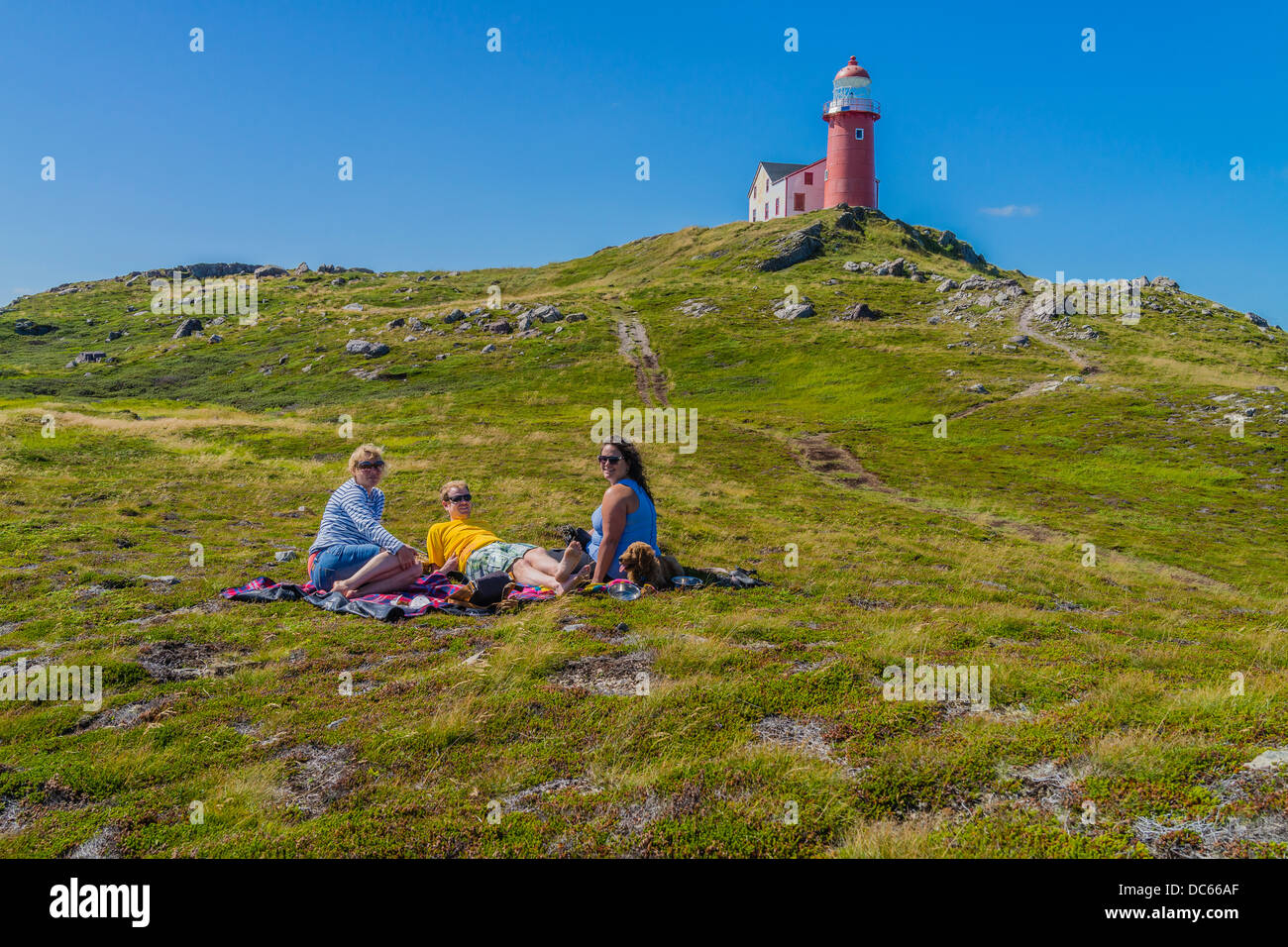 Canadians, two women and one man in their twenties, picnic outside on the ground below the Ferryland Lighthouse - Stock Image