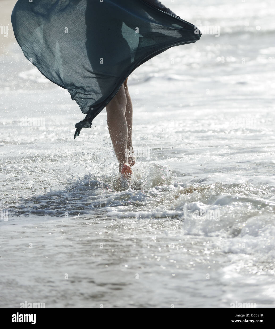 A young woman walking on the sea - Stock Image