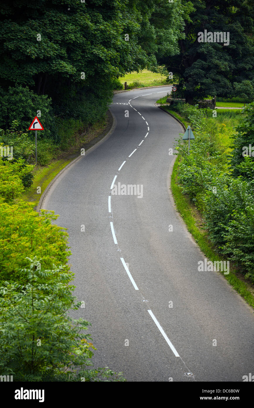 Bend on country road with sign - Stock Image