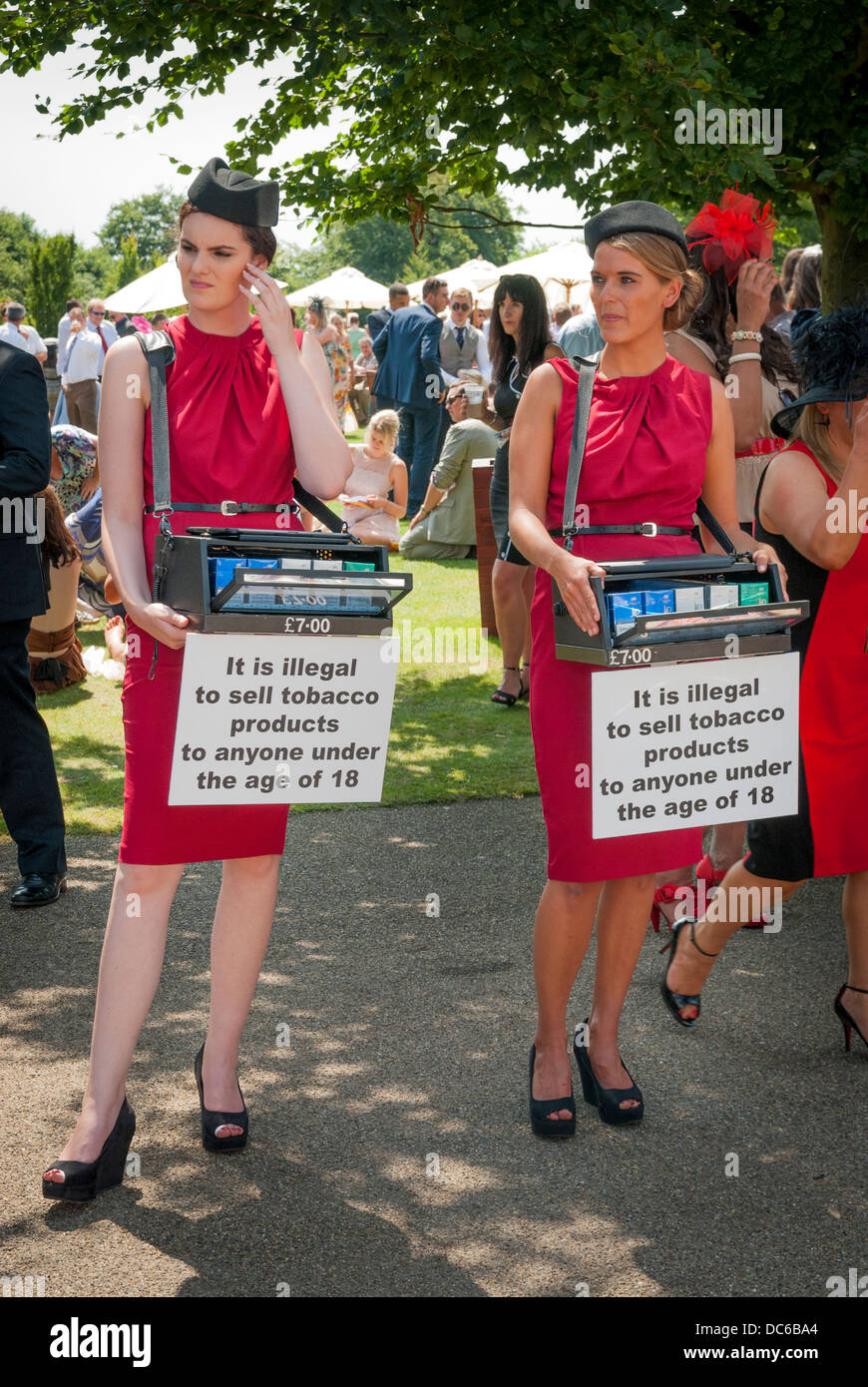 Cigarette Girls with underage prohibition signs at a racetrack. - Stock Image