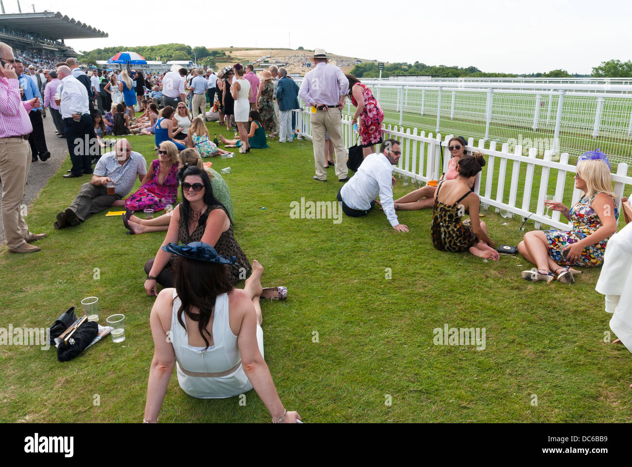 Ladies resting their feet by the rails on a horse race track - Stock Image