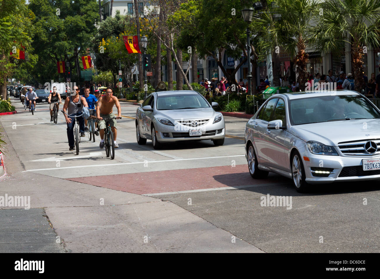 Bicyclists brave the traffic on State Street in Santa Barbara, California. - Stock Image