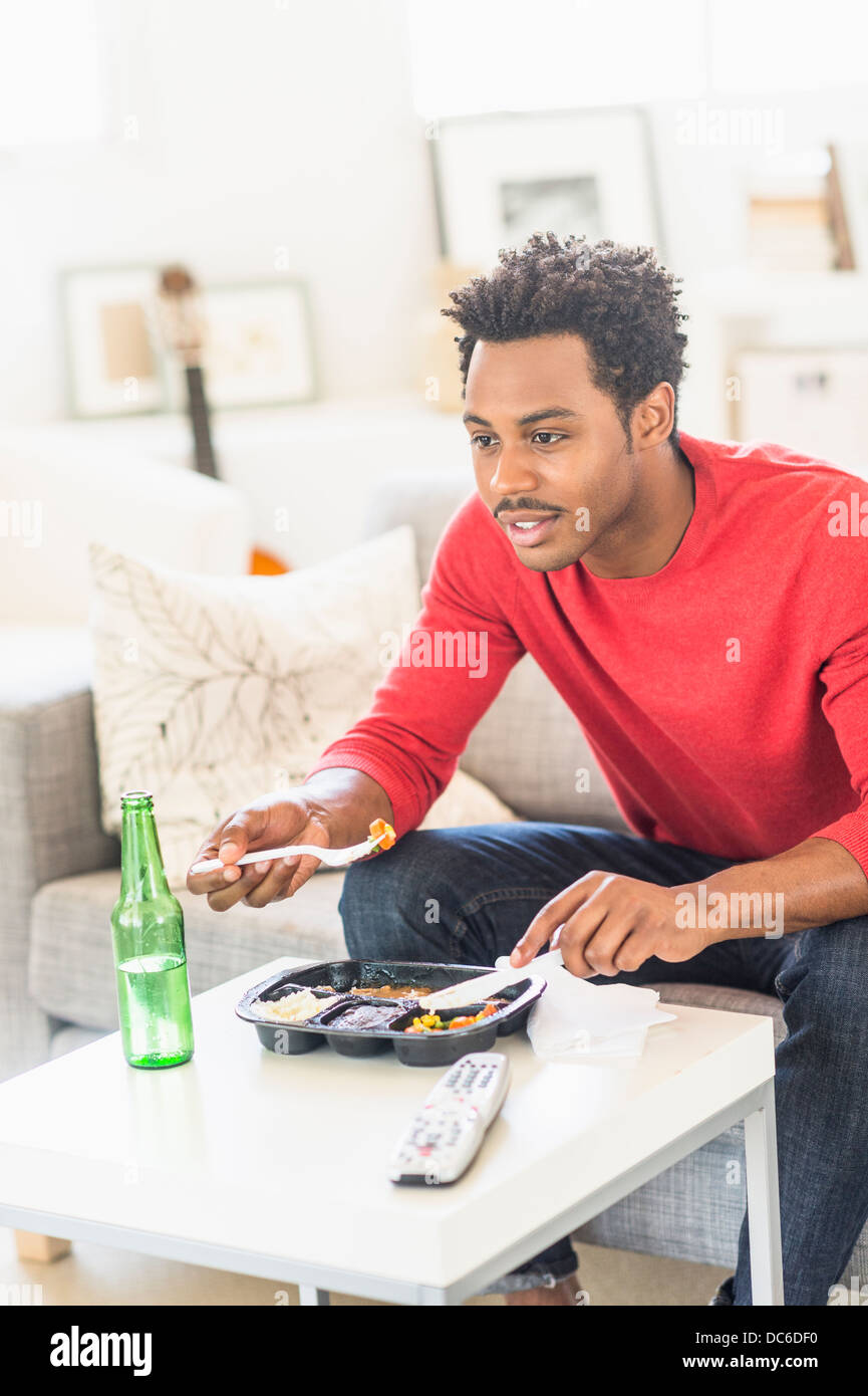 Man eating dinner and watching television - Stock Image