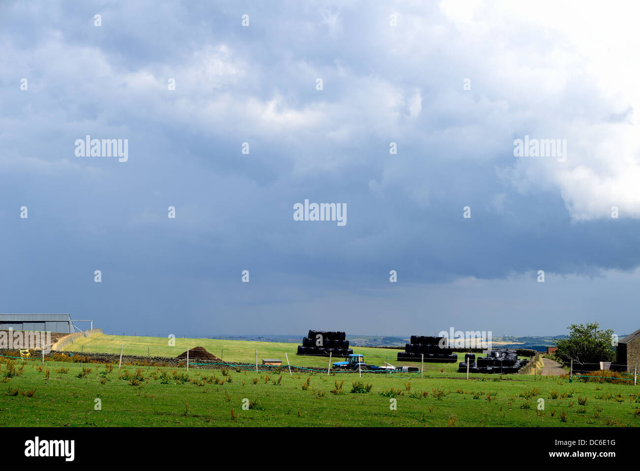 A landscape scene of a farm making bails of hay - Stock Image