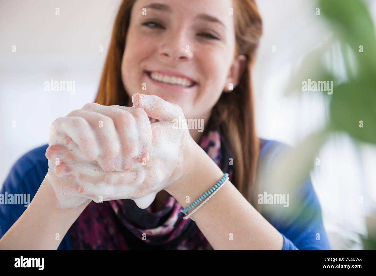 Teenage girl (14-15) washing hands - Stock Image
