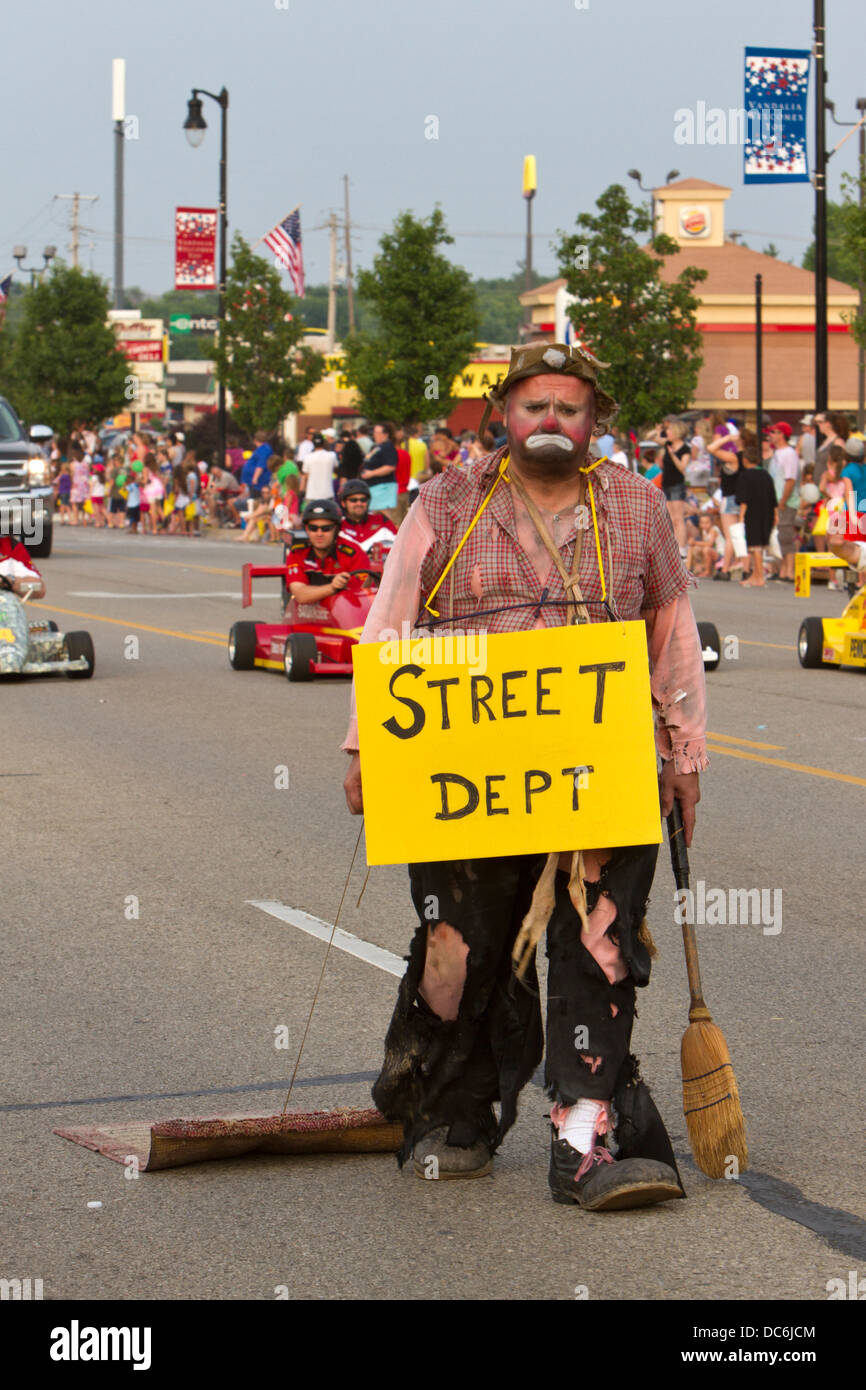 Man dresses as a hobo cleaning the streets in a parade. - Stock Image