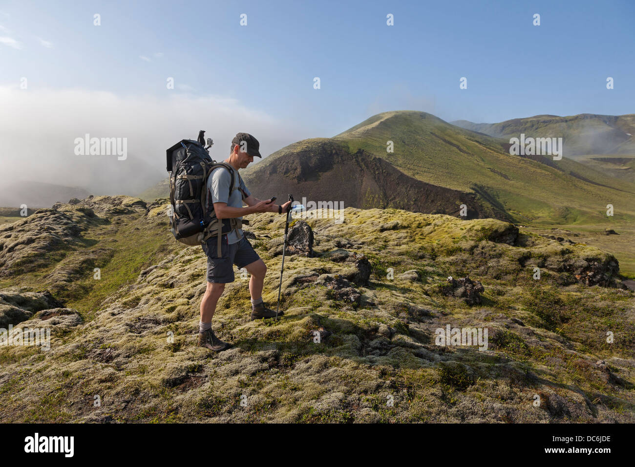 Hiker Using Smartphone While Trekking in Iceland - Stock Image