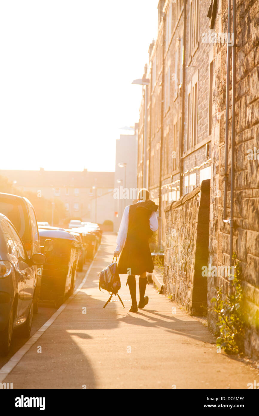 Scotsman wearing a kilt, carrying a rucksack and walking down a street in evening sun. - Stock Image