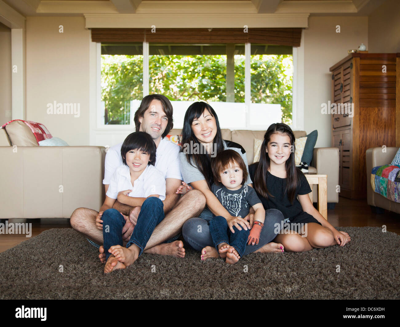 Portrait of family sitting in living room - Stock Image