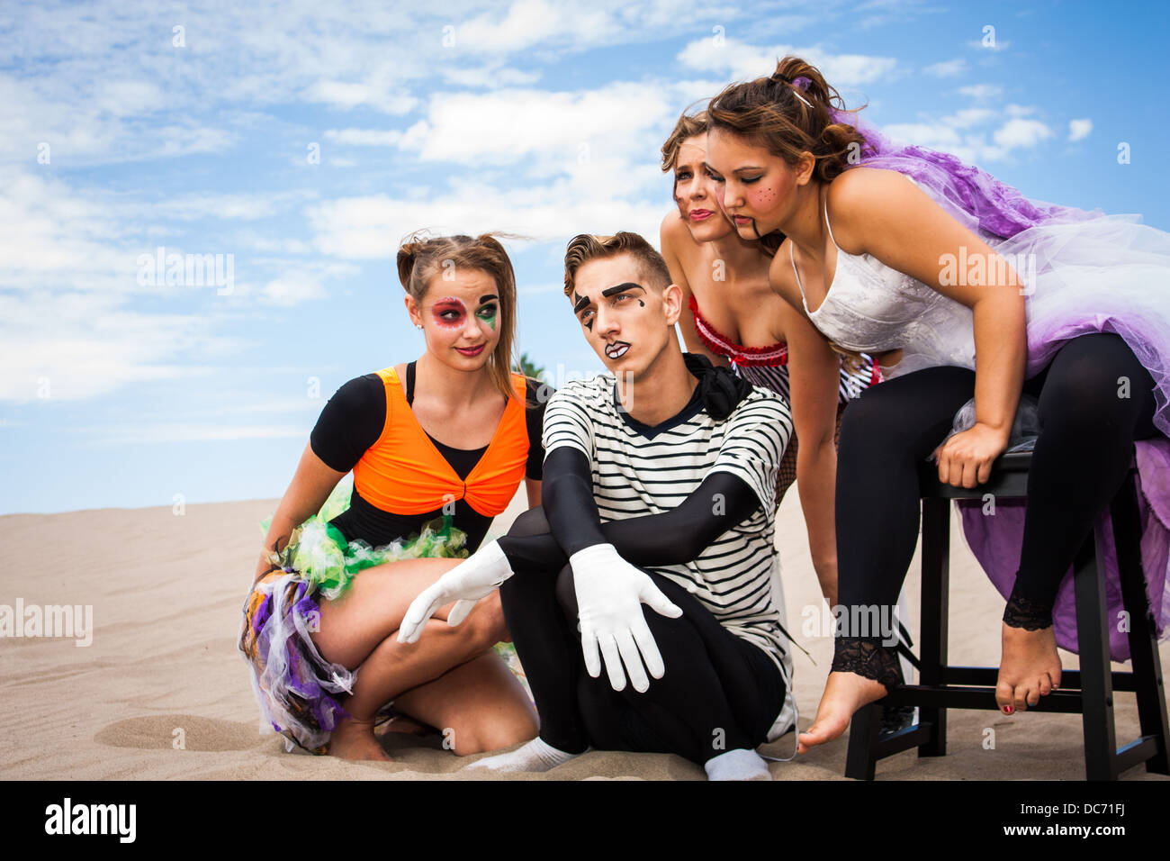 A sad and pensive young man surrounded by attentive young ladies - Stock Image