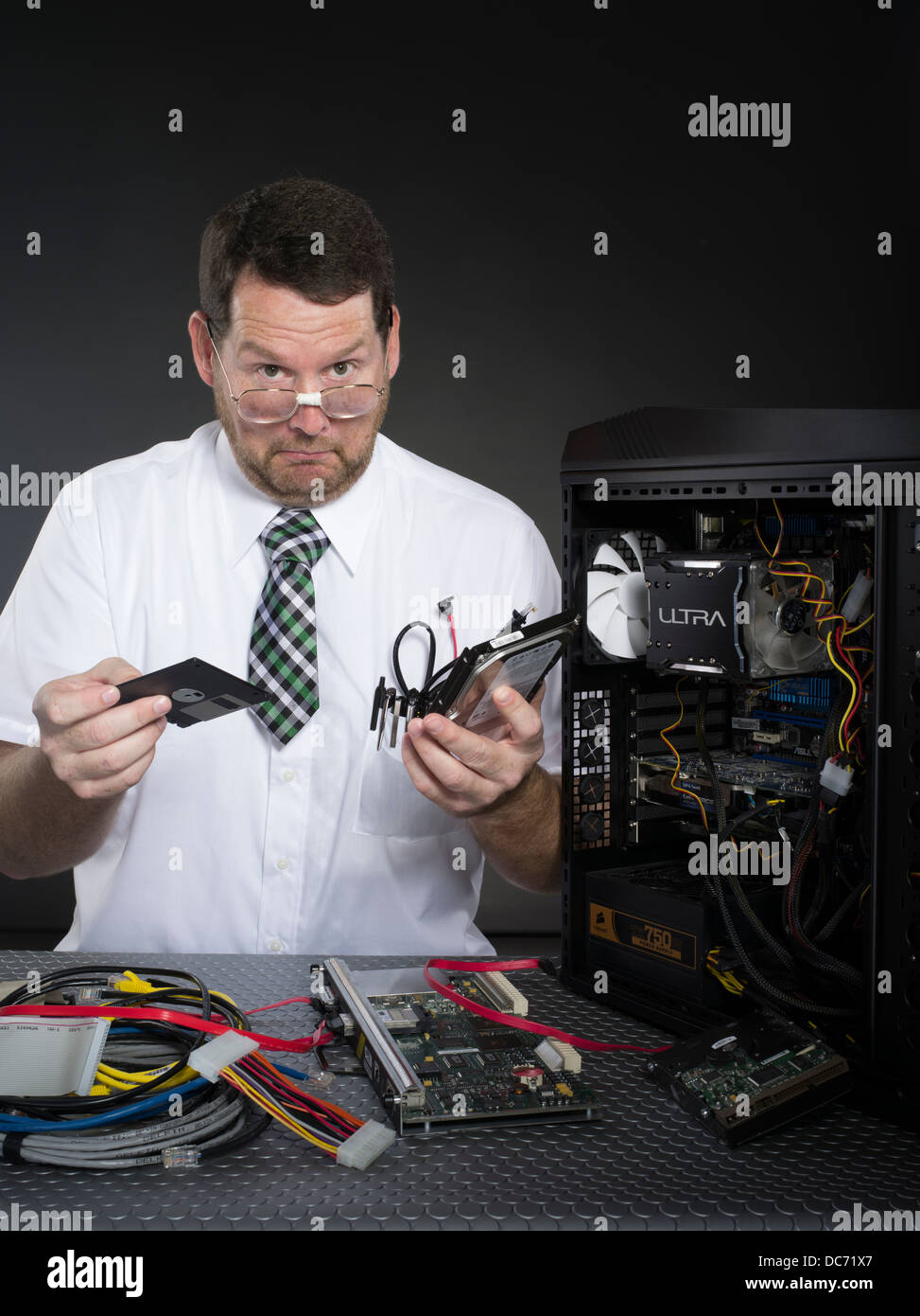 Man with computer and various hardware components - Stock Image