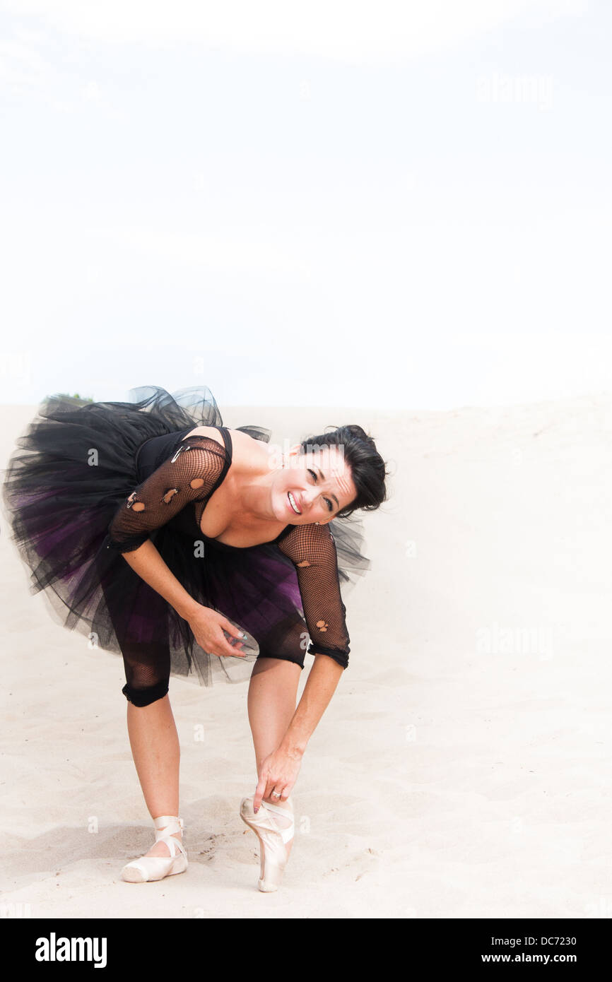 A ballerina in a tutu and pointe shoes on the desert sand leans over to stretch, lots of space for your copy. - Stock Image
