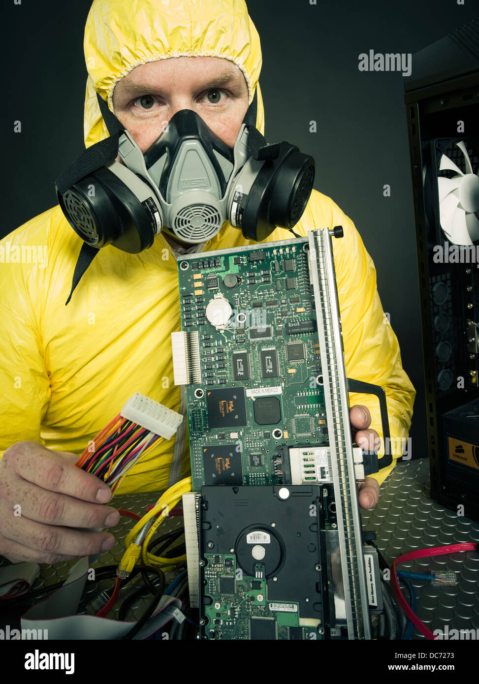 Man dealing with computer virus (figurative) or toxic chemicals heavy metals with computer and various hardware - Stock Image