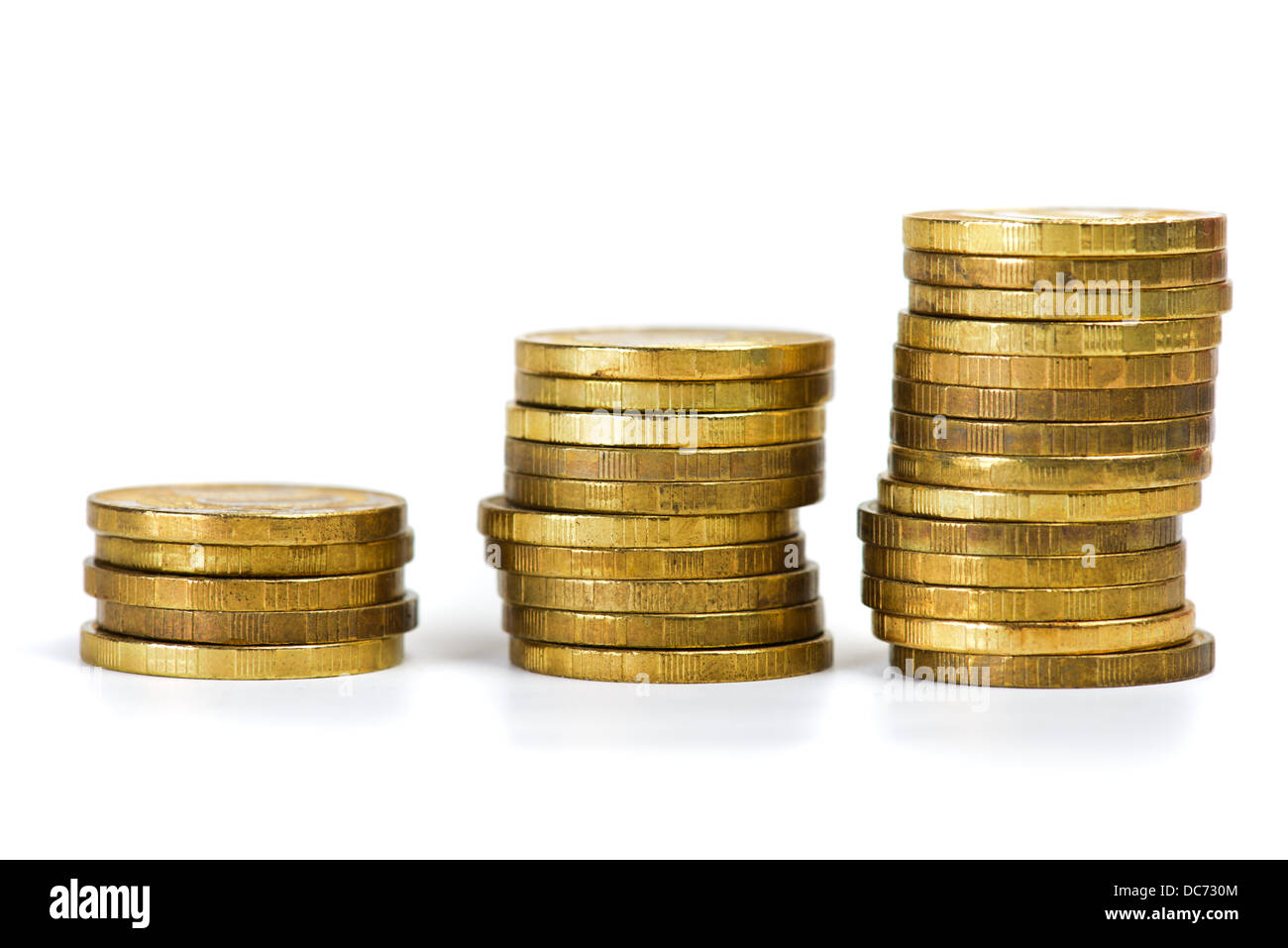Different height piles of coins isolated over white background - Stock Image