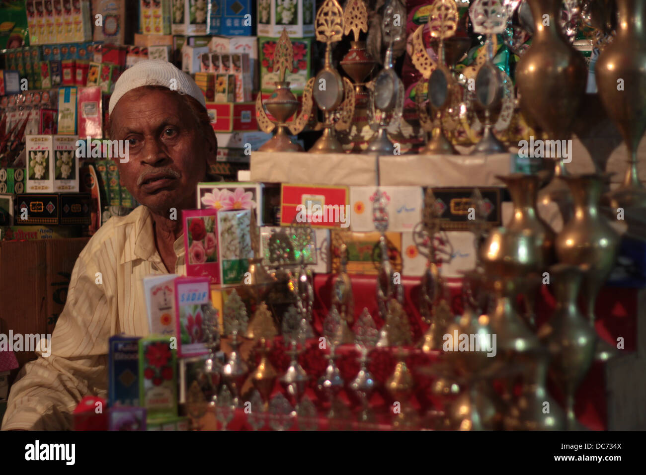 A Muslim shopkeeper sells traditional items on the occasion of Eid in Delhi, India. - Stock Image