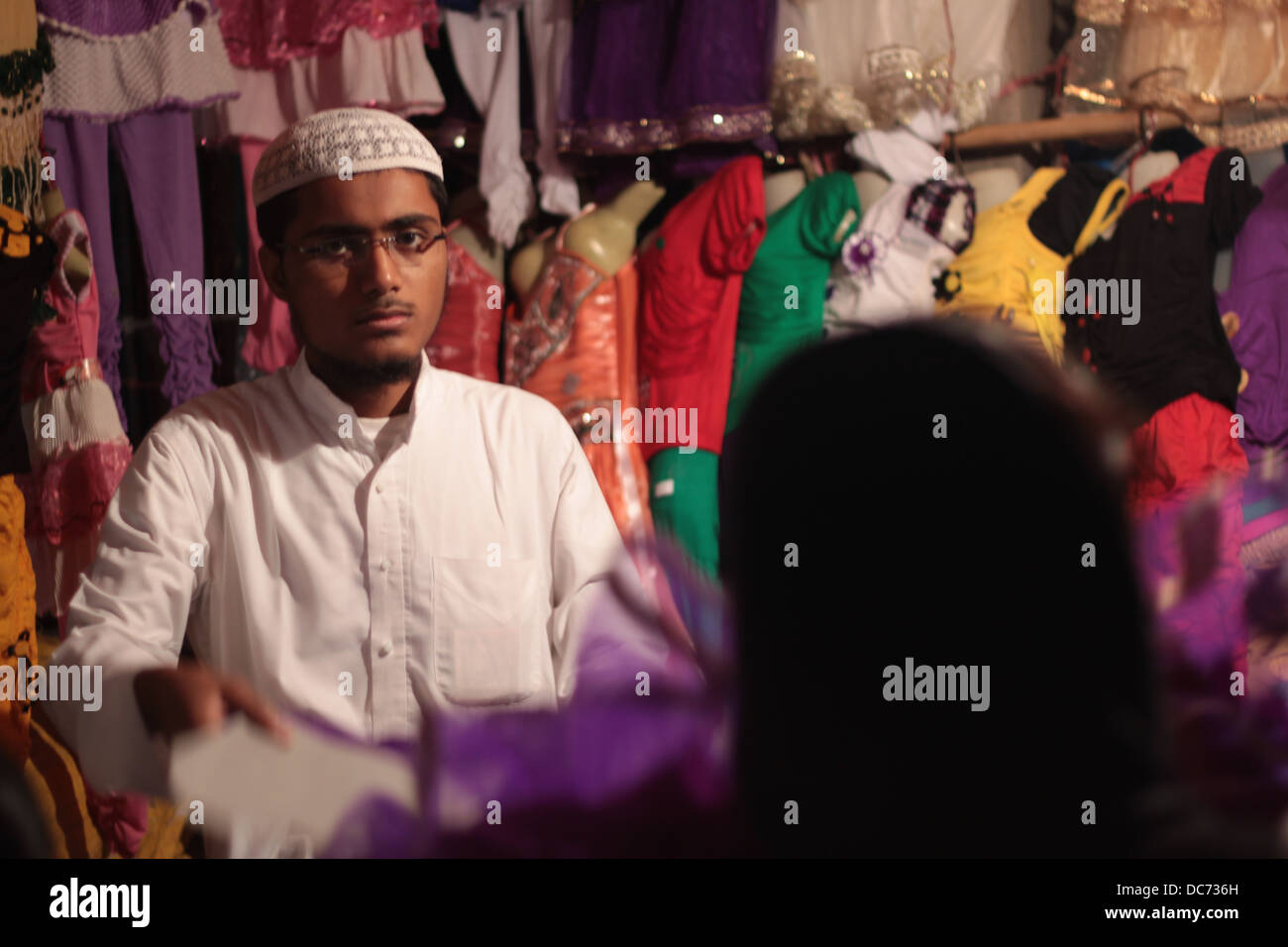 A young Muslim boy sells garments in Delhi, India, on the Eid festival. - Stock Image