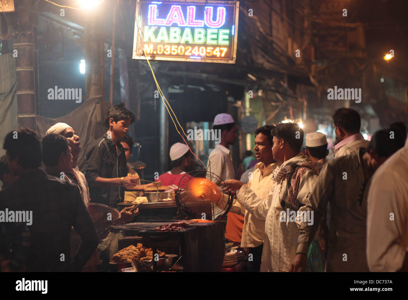 Muslims gather around a food stall in Delhi, India, on the occasion of Eid festival. - Stock Image