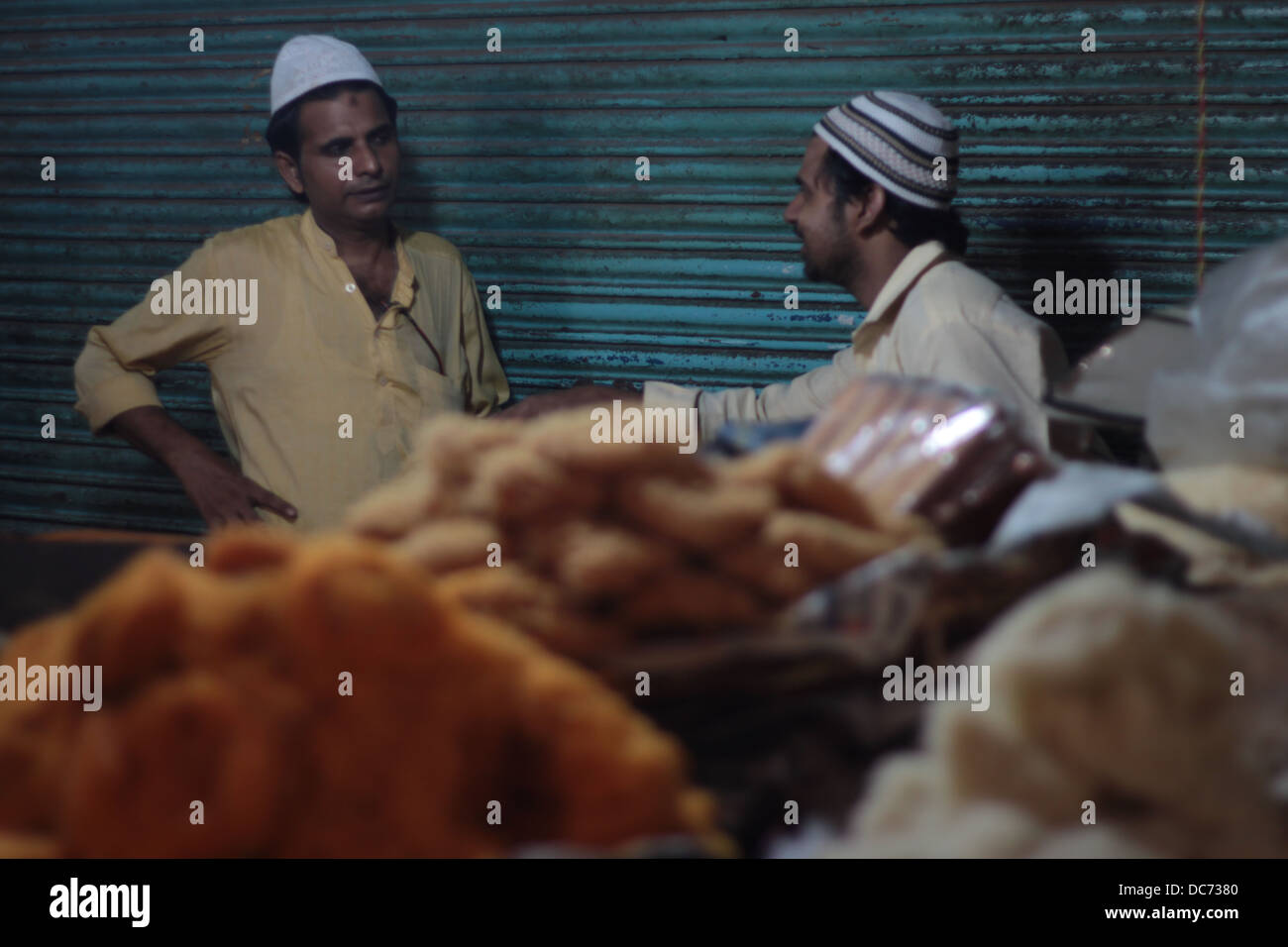 Muslim shopkeepers talk in Delhi, India, on the occasion of Eid festival. - Stock Image