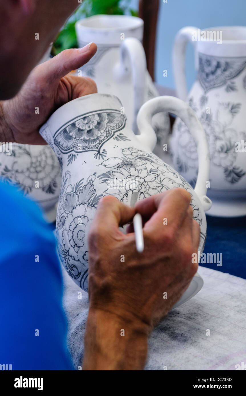 Delft, Netherlands. 5th August 2013 - Potter paints traditional blue and white Delft Pottery prior to it being fired - Stock Image