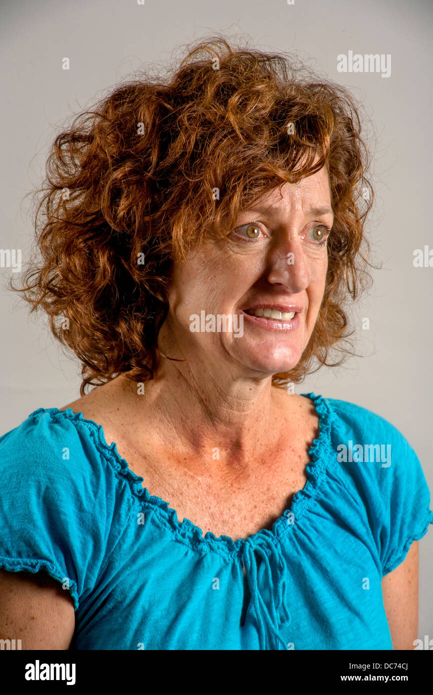A 50 year old auburn haired woman demonstrates worry and tension. - Stock Image