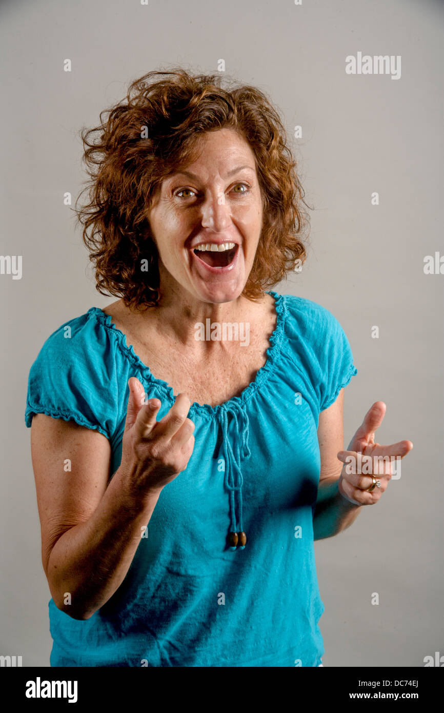 A 50 year old auburn haired woman demonstrates positive enthusiasm. Stock Photo