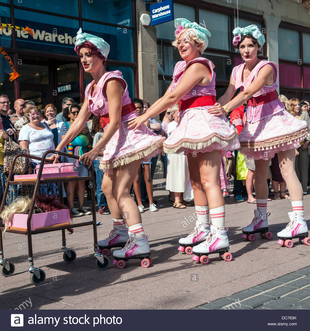 Kitsch & Sync Collective street theatre. Three women on roller skates in the streets of Cardiff, Wales, UK. - Stock Image