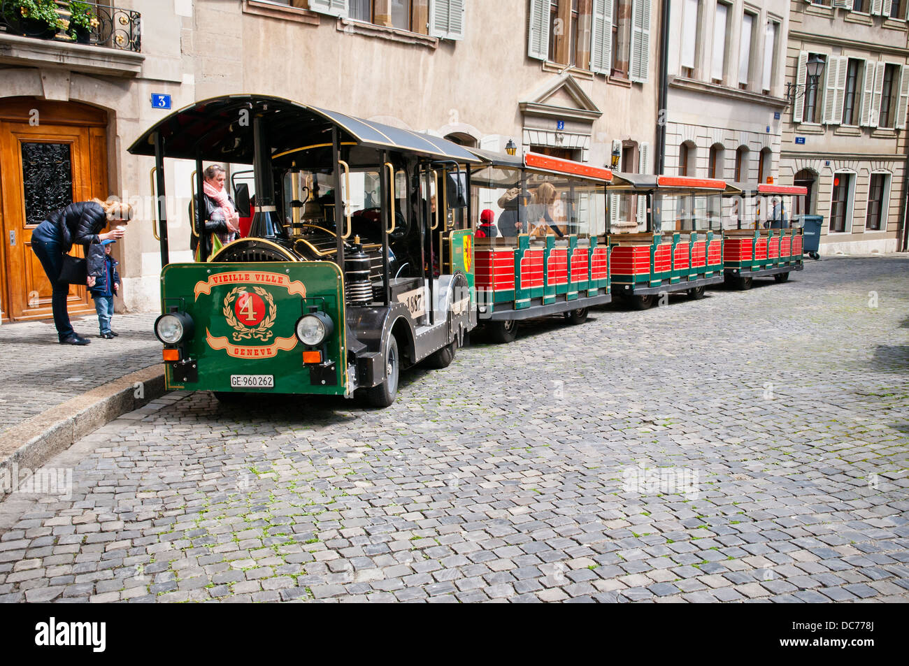 Mother and son preparing to board mini train plying the Old Town, Geneva, Switzerland, Europe. - Stock Image