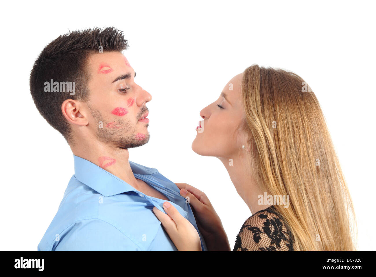 Woman trying to kiss a man desperately isolated on a white background - Stock Image