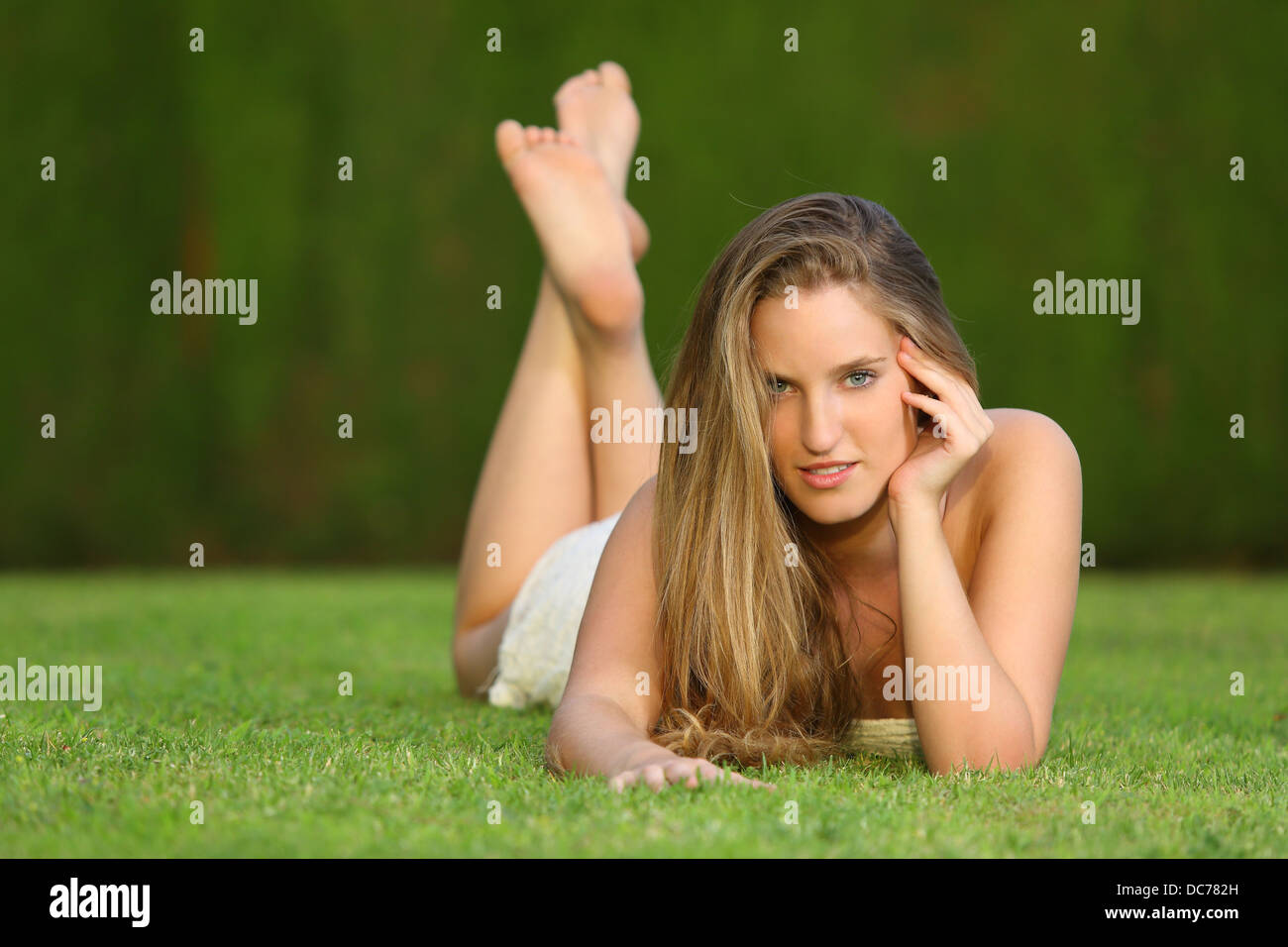 Attractive Sweet Blonde Girl Posing Lying On The Lawn In A Park Looking At Camera