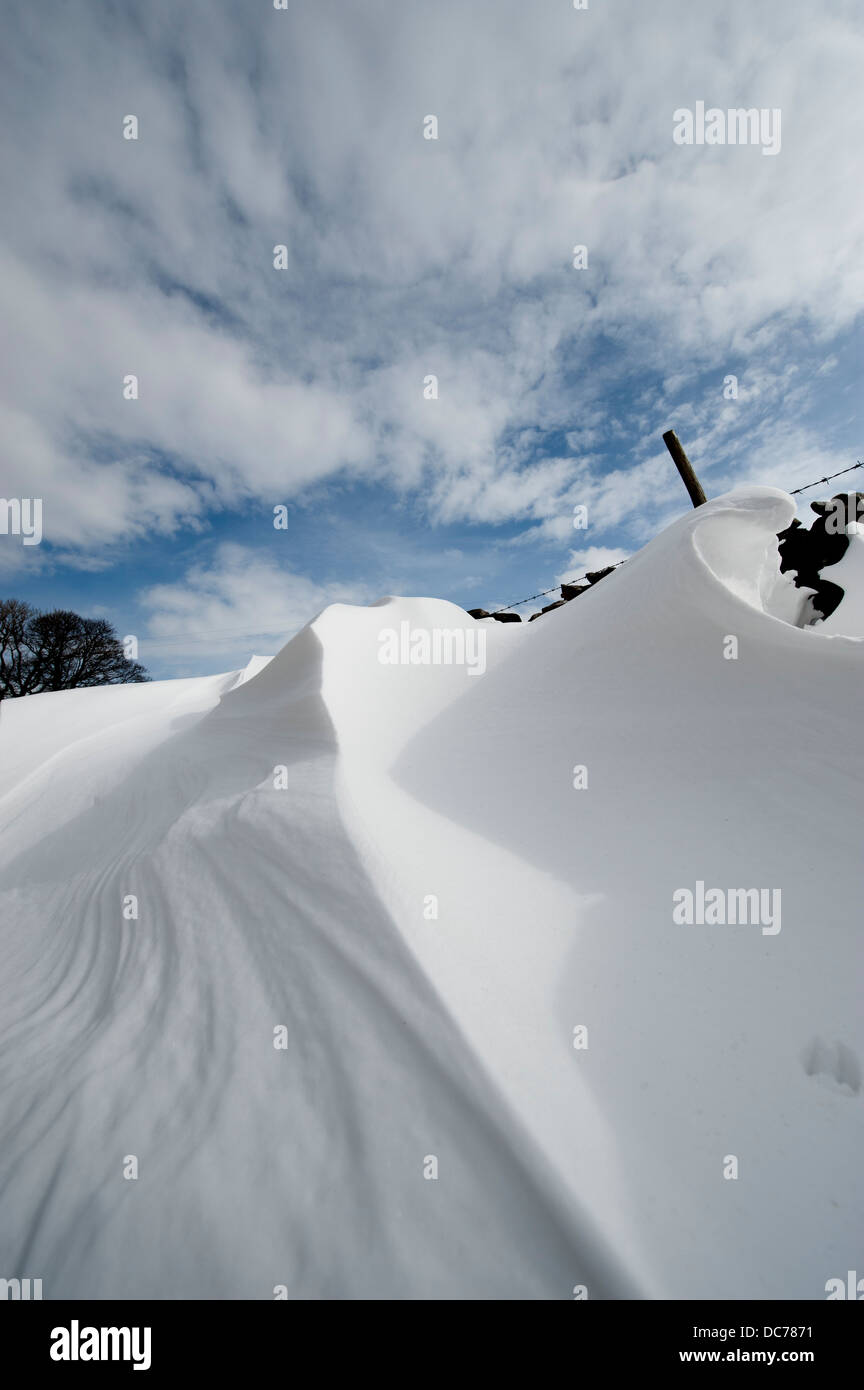 Patterns formed in snowdrifts at the back of drystone walls, Cumbria, UK - Stock Image