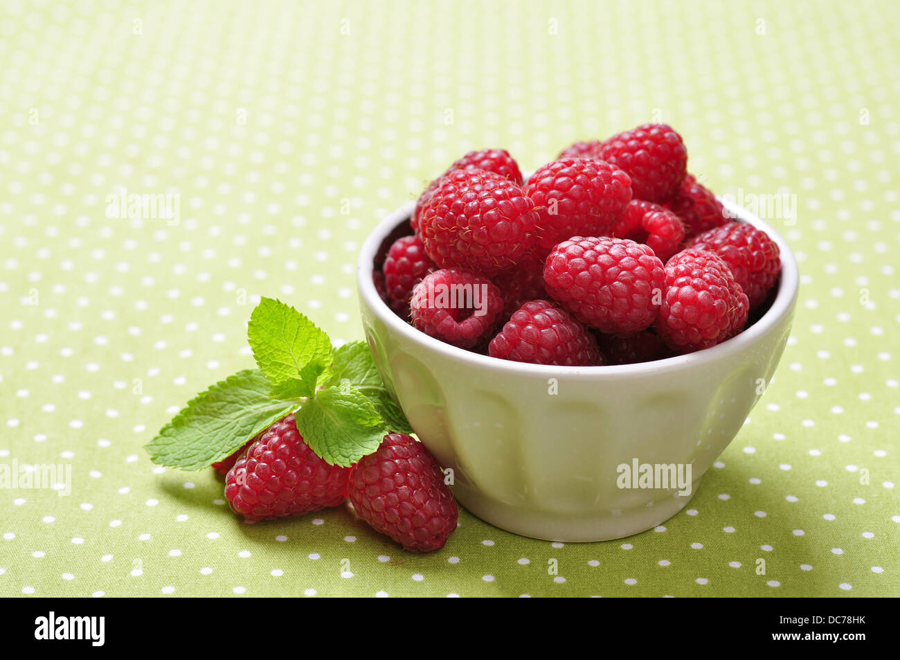 bowl of fresh raspberry on green background Stock Photo