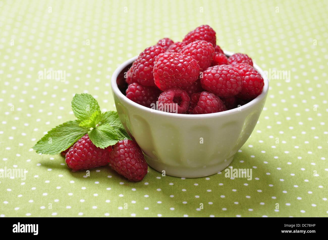 bowl of fresh raspberry on green background - Stock Image