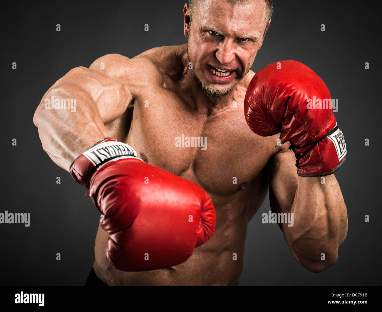 Heavyweight Boxer with red gloves punching - Stock Image